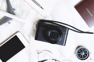 Travel accessories flatlay on marble with camera in the middle