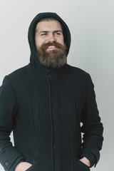 bearded happy brutal caucasian man in black jacket and hood