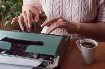 détail mains de femme sur clavier de machine à écrire ancienne