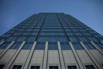 Fototapeta Tall concrete, glass and steel building surrounded by clear blue sky