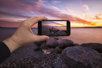 smartphone in hand photographing a sunset over the lake - these are all photographs made by me, which separately can be found on my portfolio fotolia