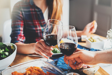 Happy romantic couple celebrating engagement, best friends making cheers with glasses of red wine while dinning at cozy home atmosphere, traditional and holidays concept