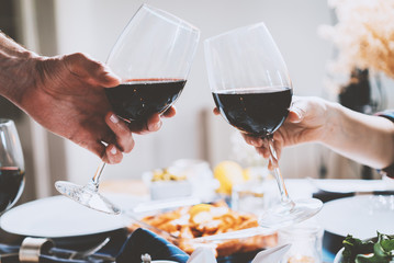 Happy romantic couple cheering with glasses of red wine at restaurant, people making cheers and celebrating anniversary or engagement, traditional or togetherness concept