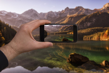 smartphone in hand photographing a mountain lake in the dolomites - these are all photographs made by me, which separately can be found on my portfolio fotolia