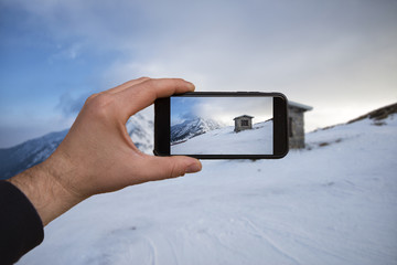 smartphone in hand photographing a snowy mountain landscape - these are all photographs made by me, which separately can be found on my portfolio fotolia