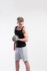 Handsome fitness man holding dumbbell, studio shot.