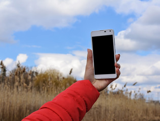 Woman hand holding smartphone against blue sky background