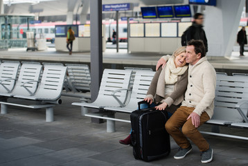 Senior couple waiting on train station, sitting on bench.