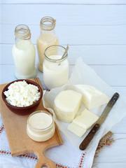 Poster de jardin Produit laitier Set of fresh dairy products on wooden background: milk, cheese, cottage, yogurt, egg, mozzarella, ryazhenka, feta.
