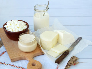 Set of fresh dairy products on wooden background: milk, cheese, cottage, yogurt, egg, mozzarella, ryazhenka, feta.
