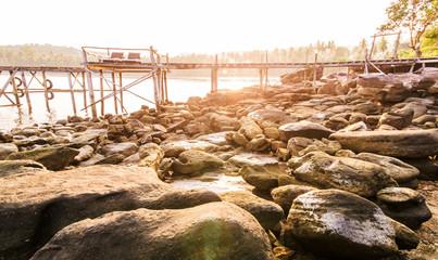 Rock beach and old wood bridge with sunset shading everithing to warm tone at kho kood thailand