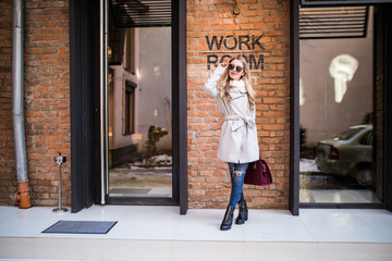 Young girl in stylish sunglasses and with a fashionable bag at work building