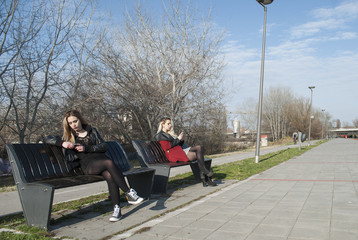Two young attractive women sitting in park