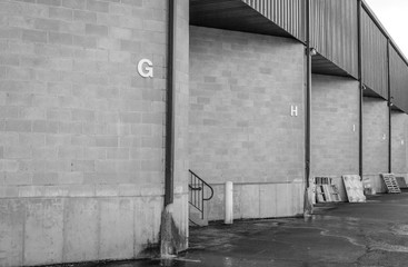 Warehouse dock garage doors. Loading dock bay garage. Storage facility loading areas. Industrial entry zones. Black and white design. Exterior architectural detail and design. Architecture detail.