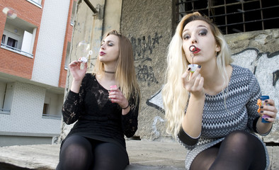 Two attractive women making soap bubbles