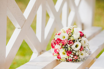 A white pink wedding bouquet of flowers rests on a white bench