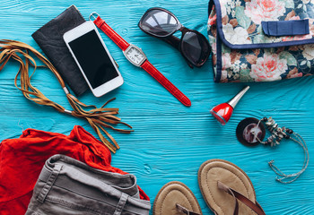 Top view of female  travel accessories set on wooden blue background with copy space