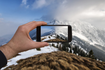smartphone in hand photographing a sunset on the snow in the mountains - these are all photographs made by me, which separately can be found on my portfolio fotolia