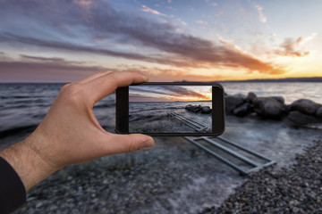 smartphone in hand photographing a sunset on the lake - these are all photographs made by me, which separately can be found on my portfolio fotolia