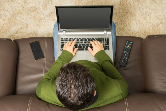 Man uses laptop on sofa. Overhead view, brown couch.