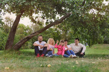Happy Family have a rest under tree apple