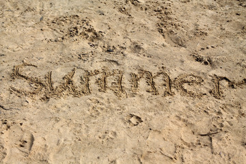 "Sand background with inscription ""Summer""."