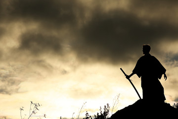 Silhouette black and white photo warrior with sword on the mountain