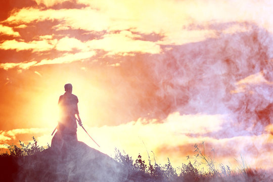 Silhouette of a warrior with a sword in the smoke of a mountain war