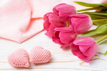 Пара вязанных розовых сердец и букет свежих тюльпанов на деревянном столе