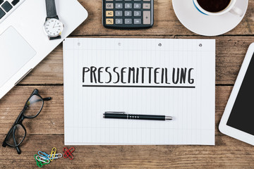 Pressemitteilung, German text for Press Release on note pad at office desk with computer technology, high angle