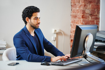 An Arab man in a jacket sitting in the workplace at the computer and typing on keyboard in office