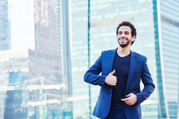Arab man in suit shows gesture thumbs up on the background of skyscrapers