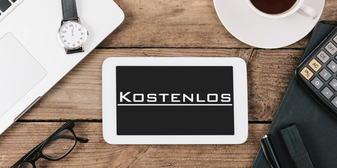 Kostenlos, German text for Free on screen of tablet computer at office desk