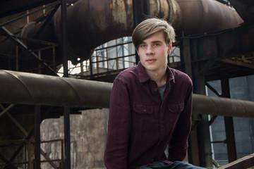 Teen boy in heavy industry area