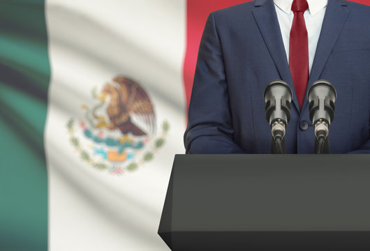 Businessman or politician making speech from behind a pulpit with national flag on background - Mexico