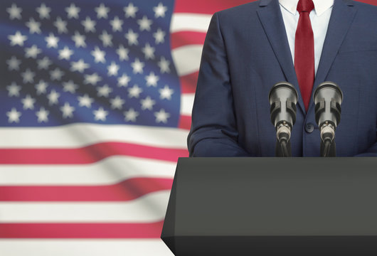 Businessman or politician making speech from behind a pulpit with national flag on background - United States