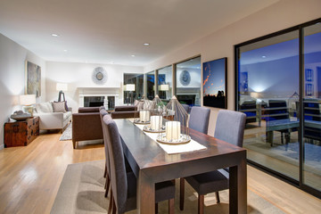 Grey tones dining space with glass doors to large upper deck