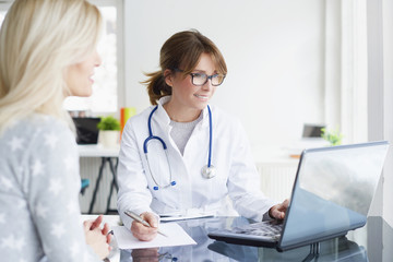 Doctor and her patient. Shot of a middle aged female doctor sitting in front of laptop and consulting with her patient.