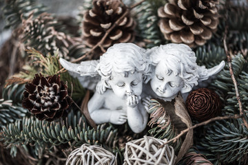zwei Engelsfiguren in einem Weihnachtsgesteck auf einem Grab