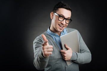 Positive delighted office worker holding notebook