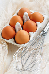 Fresh brown eggs with stainless steel whisk.
