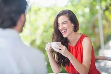Beautiful woman laughing while having coffee