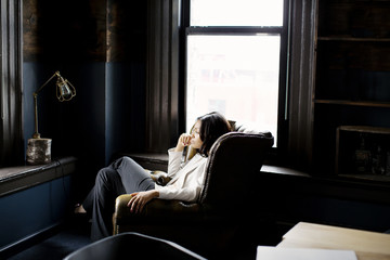 Thoughtful businesswoman sitting in armchair