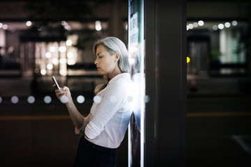 Businesswoman leaning on bus stop and using smart phone