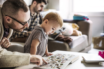 Father watching book with daughter at home