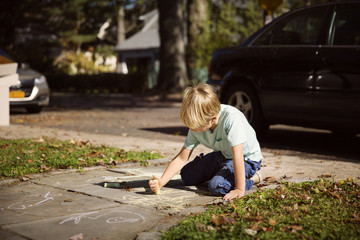 Boy (6-7) drawing on pavement