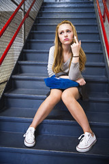 Girl (12-13) sitting on stairs