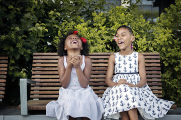 Two girls (4-5, 6-7) laughing on bench