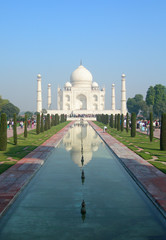 Iconic perspective of the Taj Mahal mausoleum in Agra, India, with the main building dome framed by the minaret towers reflected in the pool.