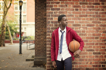 Teenager leaning against brick wall with basketball under arm